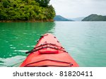 Red touring kayak in green waters of the Marlborough Sounds, New Zealand - stock photo