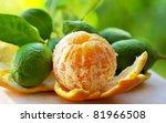 Peeled orange, and green lemons - stock photo