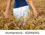 Abundance in life concept - woman walking through wheat field touching the spikes - stock photo