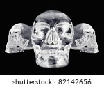 3 views of a crystal skull on a black background - stock photo