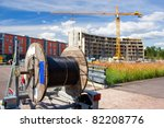 A reel of heavy coaxial cable used for cable-TV underground construction, and the construction site in the background - stock photo
