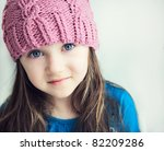 Close-up portrait of adorable smiling child girl wearing pink knitted hat - stock photo