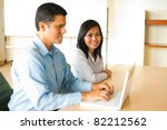 Attractive Asian female smiling, sitting at conference room desk in background looking at camera, meeting with Hispanic male businessman coworker working, looking at a laptop in office. Horizontal - stock photo