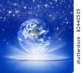 the planet Earth in rays of light over starry sky like a spiritual concept - stock photo