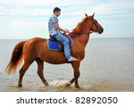 Man Riding On A Brown Horse In...