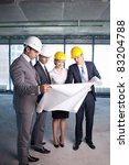Businessmen look at a building site plan - stock photo