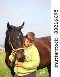 teenager boy hugging brown horse | Shutterstock . vector #83216695
