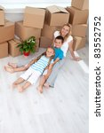 Family relaxing in their new still empty home sitting on the floor - top view - stock photo