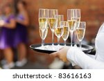 Waiter serving champagne at festive event - stock photo
