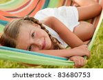 Happy childhood - Cute girl in colorful hammock - stock photo