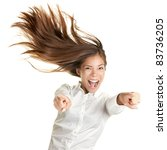 happy crazy excited woman screaming and pointing at camera with wild long hair in the wind. Beautiful ecstatic mixed race Caucasian Asian female model. - stock photo
