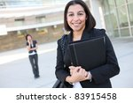 An attractive hispanic business worker with co-worker in background - stock photo