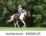 Stock photo teenage girl riding a running horse 84008125