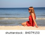 Young woman sitting on a sunny beach - stock photo