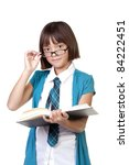 A school girl holds a book in her hand as she looks up. - stock photo