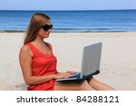 Young woman with laptop is sitting on the sunny beach. - stock photo