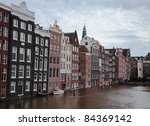 Stock photo buildings on the water in amsterdam and gloomy sky 84369142
