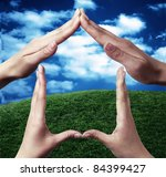 Conceptual symbol home made with hands by two people with nature in the background - stock photo