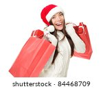 Christmas shopping woman holding shopping bags with gifts. Happy and smiling wearing red santa hat isolated on white background. Mixed race Caucasian / Chinese Asian female model. - stock photo
