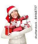 Christmas shopping woman holding gifts smiling happy looking up to side isolated on white background. Santa girl wearing sweater and santa hat holding presents. Mixed race Asian Caucasian female model - stock photo