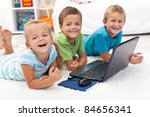 Happy healthy kids with laptop computer laying on the floor - stock photo