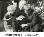 Vintage photo of mother reading with children (fifties) - stock photo