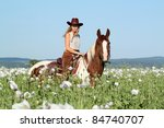 Pretty woman posing on horse in the poppy field - stock photo