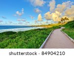 Tropical sunset near the ocean. Beautiful green grass and island view with pathway. - stock photo