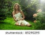 Cute young lady holding a puppy dog - stock photo