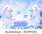 two praying angels with rays of light over blue sky with stars - stock photo