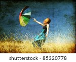 Redhead girl with umbrella at windy grass meadow. Photo in old color image style.