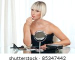 attractive woman putting lipstick at her home - stock photo