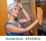 attractive woman cleaning and dusting at her home - stock photo