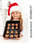 Happy christmas girl baking cookies in the kitchen showing the results - stock photo