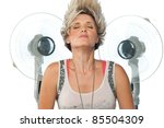 beauty portrait of young woman in front of electric fan - stock photo