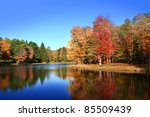 Colorful tree reflections in beautiful lake in Autumn - stock photo