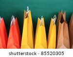paper Shopping yellow eco orange gift bags on green background ecological - stock photo