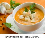 A bowl with pumpkin cream soup with crouton. Selective focus - stock photo