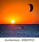 silhouette of a man with a kite at sunset - stock photo