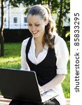 Pretty girl with laptop in a park - stock photo