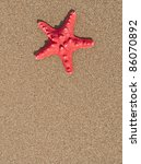 Red sea star shell on sand background - stock photo
