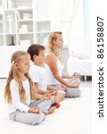 Family sitting in a row meditating - happy, healthy and balanced life concept - stock photo