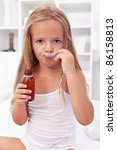 Sick little girl taking medication on her own - stock photo