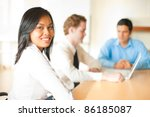 A beautiful Asian business woman smiling looking over shoulder at camera meeting with two male colleagues team members sitting at conference room table. Horizontal - stock photo