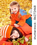 Happy family with child on autumn orange leaves. Outdoor. - stock photo