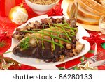 whole carp baked with mushrooms and red onion  and chives decoration  on  christmas table - stock photo