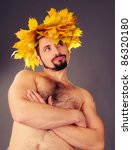 Portrait of a handsome man with a wreath of autumn leaves on the head. - stock photo