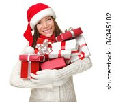 Christmas shopping woman holding many Christmas gifts in her arms wearing santa hat and winter clothing. Beautiful young female model isolated on white background. - stock photo