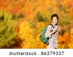 Hiking woman in Fall forest. Female hiker looking around in forest in autumn colors. Beautiful young woman on hike. - stock photo