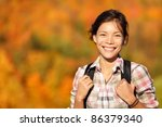 hiker hiking in Autumn forest. Young outdoors woman smiling happy during hike in beautiful fall colored forest. Fresh Mixed race Chinese Asian Caucasian female model. - stock photo